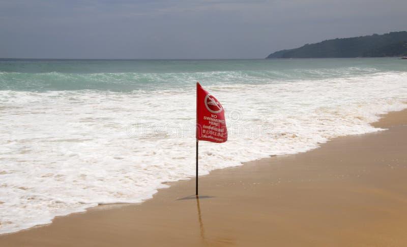 Geen hier het Zwemmen van rode vlag op een strand in Phuket, Thailand De waarschuwingsinschrijving is in de Engelse, Thaise en Ru stock afbeelding