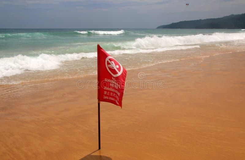 Geen hier het Zwemmen van rode vlag op een strand in Phuket, Thailand De waarschuwingsinschrijving is in de Engelse, Thaise en Ru stock fotografie
