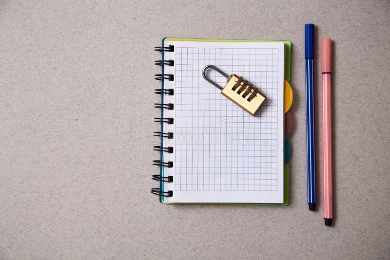 Geen idee of inspiratieconcept: slot die op een notitieboekje en gekleurde pennen op een grijze achtergrond liggen royalty-vrije stock foto's