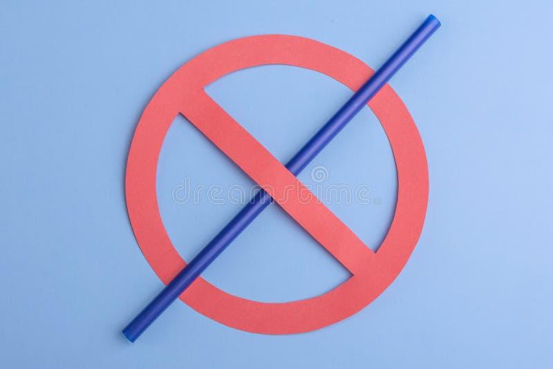 geen plastiek Klein blauw stro in verbodsteken over een blauwe achtergrond, die een teken van geen plastic stro toe te schrijven  stock fotografie