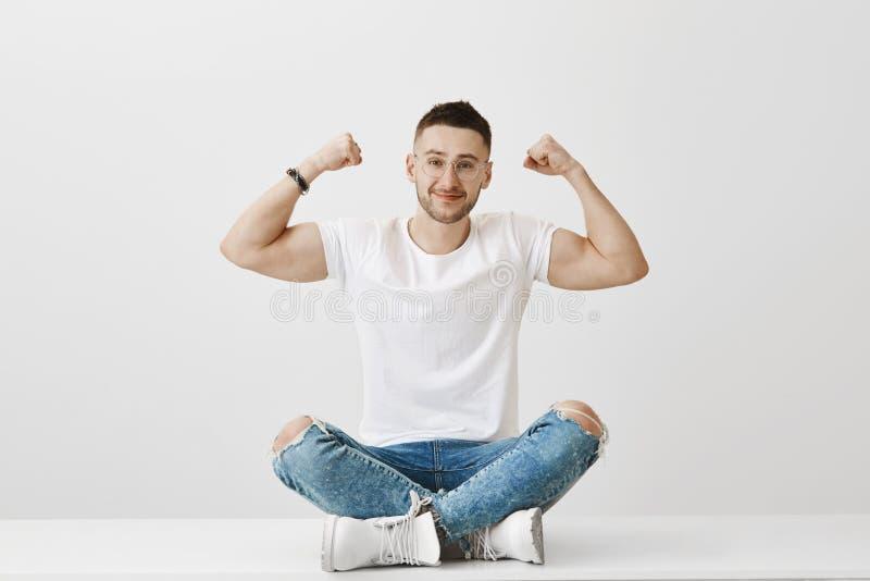 Geen steroïden enkel partijen van inspanning en macht van zullen Vriendschappelijk-kijkend sterke mens die in glazen op vloer zit stock afbeeldingen