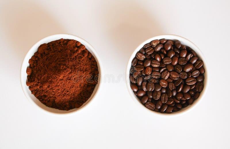 Geerdeter Kaffee und Kaffeebohnen in den Schalen lokalisiert auf Weiß stockbilder