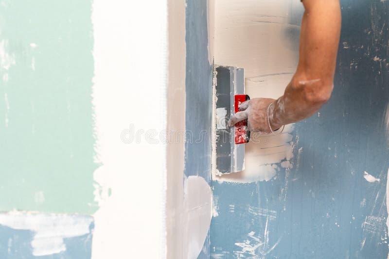 Geerntet nah herauf Foto der Berufsschlosserhand mit der vergipsenden Spachtel und Wand innerhalb des Raumes mit Gipselement umge stockfotografie