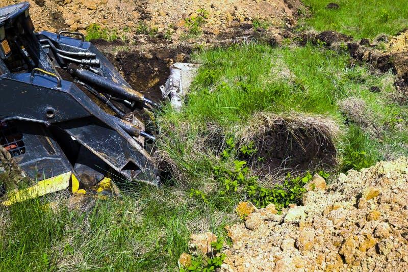 Geerntete Ansicht der grabenden Grube des Miniladers während der Erdarbeiten über grasartiges Feld stockfotografie