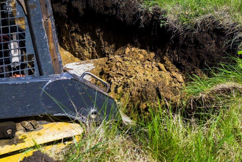 Geerntete Ansicht der grabenden Grundlagengrube des Baggers auf dem grasartigen Gebiet in der Landschaft stockfotografie