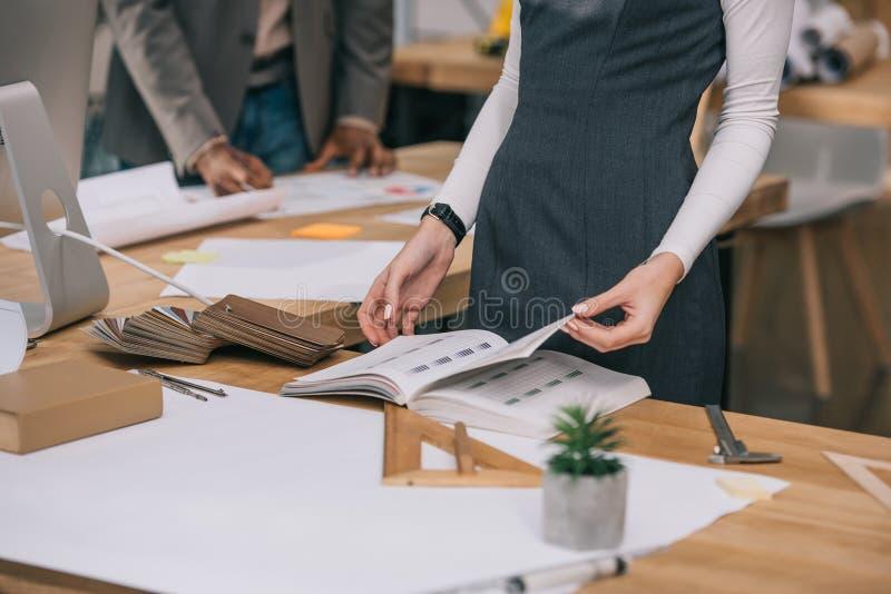 geerntete Ansicht des Architektenlesebuches am Arbeitsplatz stockfotografie