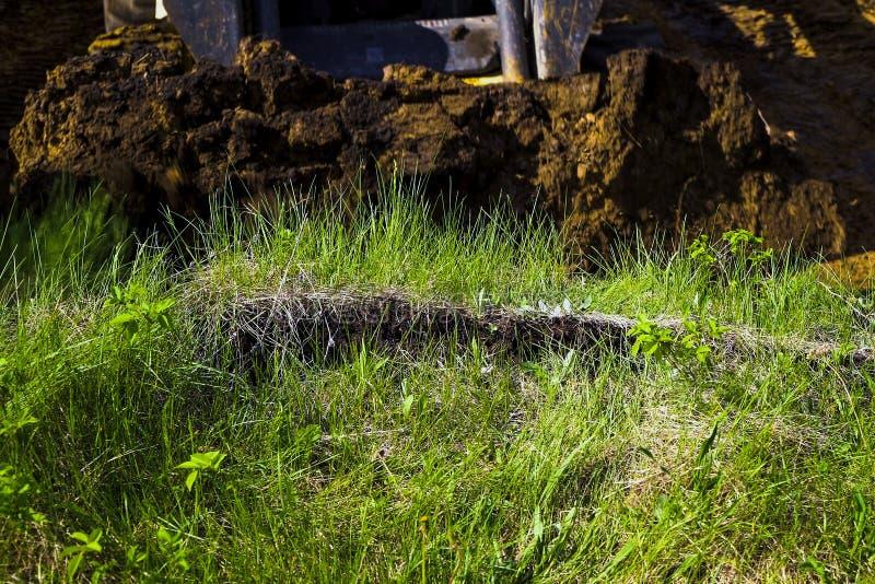 Geerntete Ansicht des Planierraupeneimers grabend in grasartiges Feld an den Aushubarbeiten lizenzfreie stockbilder