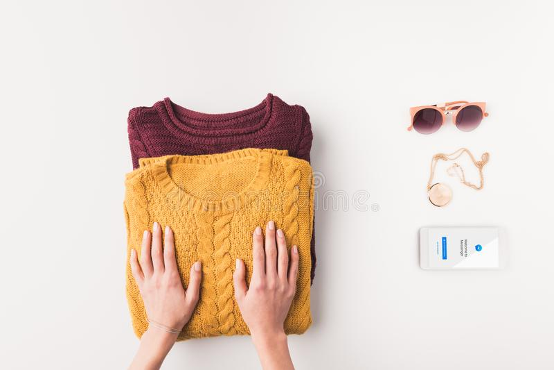 geerntete Ansicht von weiblichen Händen mit Strickjacken, Sonnenbrille und Smartphone mit facebook Botegerät, lizenzfreies stockfoto