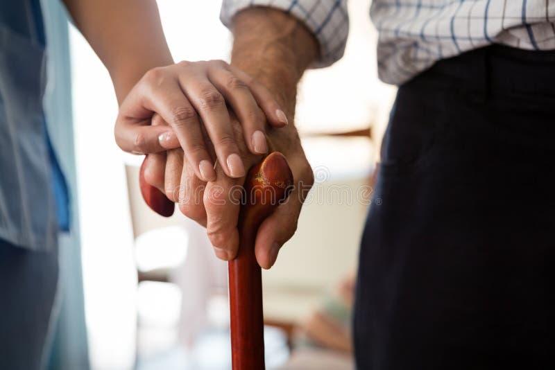 Geerntete Hände der Ärztin und des älteren Mannes, die gehenden Stock halten stockfotografie