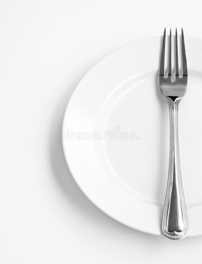 Geerntete weiße Platte und Gabel auf Weiß stockfotografie