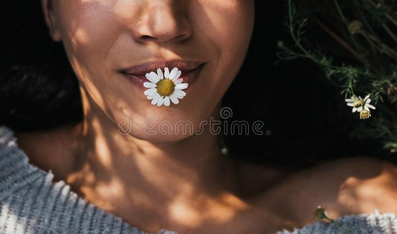 Geernteter horizontaler Schuss der Nahaufnahme des brunette jungen Mädchens mit Gänseblümchenblume im Mundfreien Natur genießend  lizenzfreies stockfoto