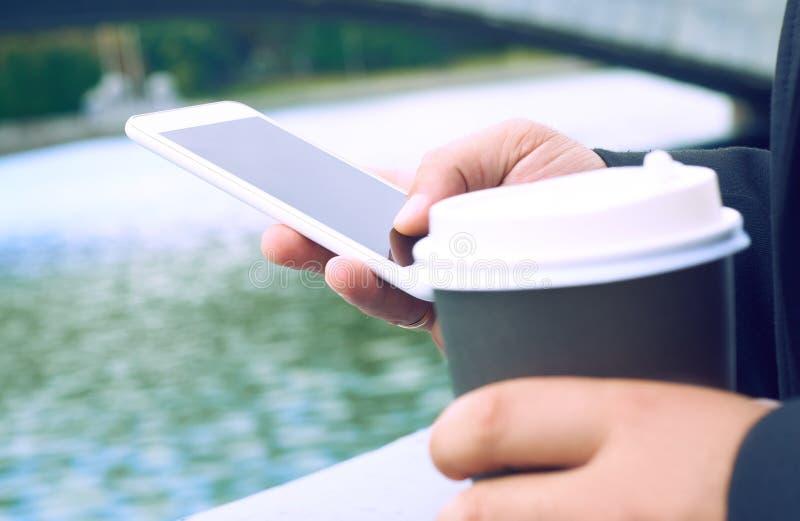 Geernteter junger Mann des Bildes, der am Tisch mit Tasse Kaffee und intelligentem Telefon, Mann ` s Hände schreiben Mitteilung a stockfotos