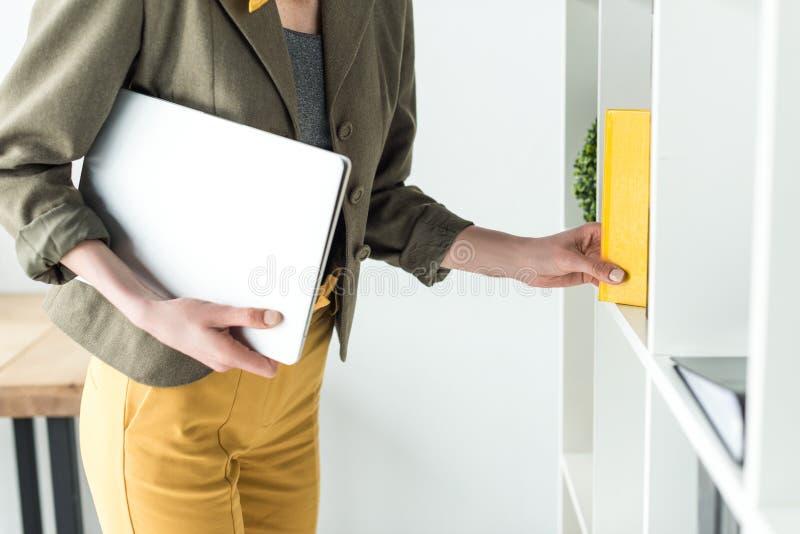 geernteter Schuss der Geschäftsfrau Laptop halten und Buch vom Regal nehmend lizenzfreies stockfoto