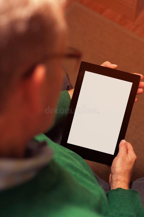 Geernteter Schuss des älteren Mannes arbeitend mit Tablette lizenzfreies stockbild