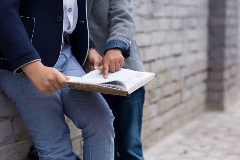 geernteter Schuss des Buches mit zwei Schülern Lesezusammen lizenzfreies stockbild