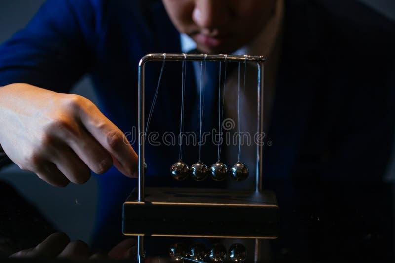 Geernteter Schuss des Geschäftsmannes Ball von Newton-Wiege ziehend stockfotos