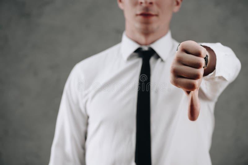 geernteter Schuss des Geschäftsmannes Daumen unten zeigend lizenzfreie stockbilder
