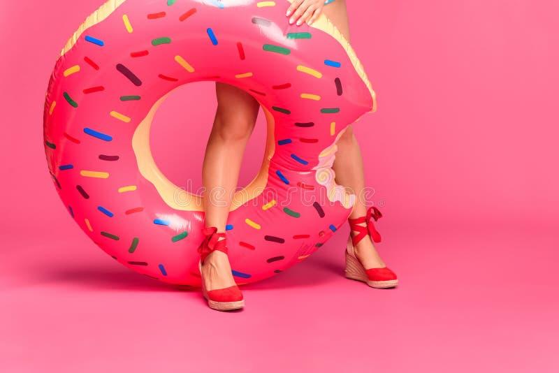 geernteter Schuss des Mädchens in den roten Schuhen, die aufblasbaren Ring halten lizenzfreies stockfoto