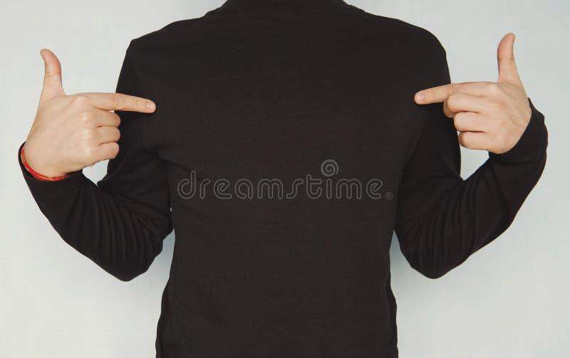 Geernteter Schuss des schönen jungen unrasierten Mannes, der zufällige Kleidung, Finger auf Kopienraum auf seinem schwarzen leere lizenzfreies stockfoto
