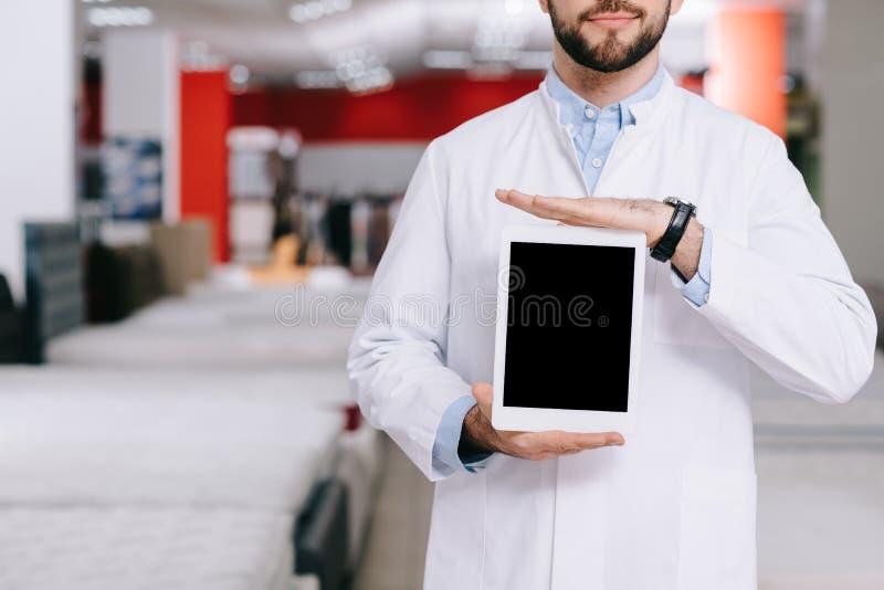 geernteter Schuss des Verkäufers im weißen Mantel, der Tablette mit leerem Bildschirm im Möbelshop zeigt lizenzfreie stockbilder