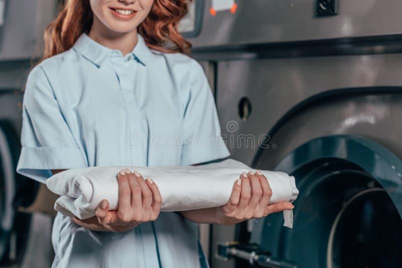 geernteter Schuss des weiblichen Trockenreinigungsarbeitskraftholdingstapels von sauberem stockbild
