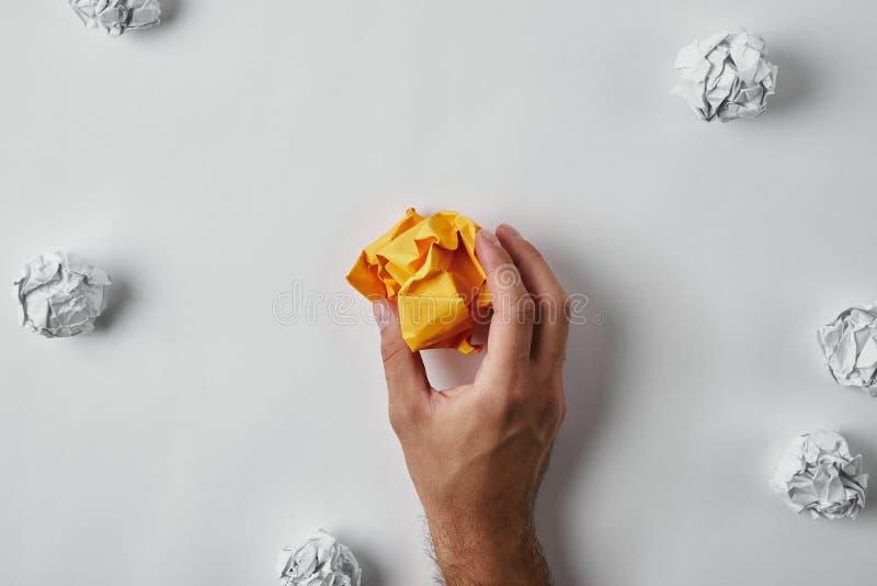 geernteter Schuss des zerknitterten gelben Papiers des Mannes Holding, das mit Weiß umgeben wurde, zerknitterte Papiere lizenzfreie stockfotos