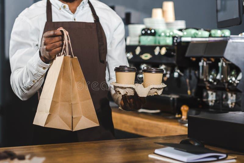 geernteter Schuss von Afroamerikaner barista Wegwerfkaffeetassen und Papiertüten im Café halten lizenzfreie stockbilder