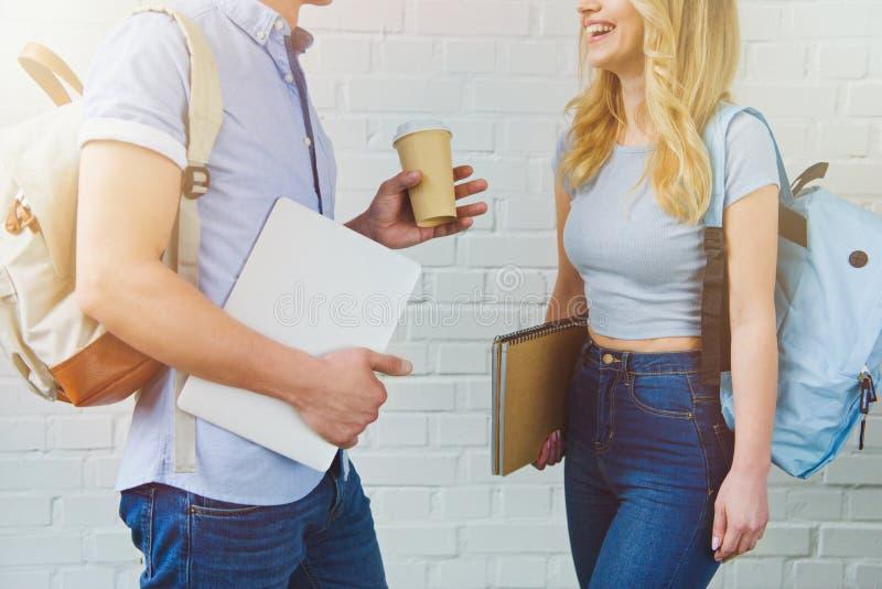 geernteter Schuss von den jungen Studenten, die auf Kaffeepause vor Weiß plaudern lizenzfreies stockbild