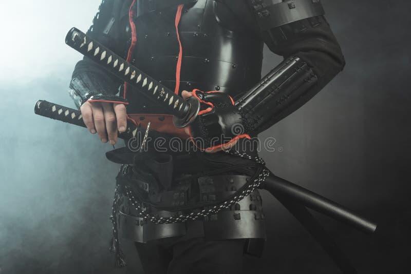 geernteter Schuss von Samurais in der Rüstung mit Klingen auf dunklem Hintergrund lizenzfreies stockfoto