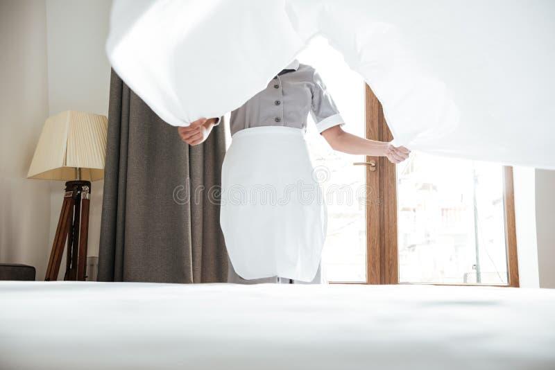 Geerntetes Bild ändernden Bettlaken des Hotelmädchens lizenzfreie stockfotografie