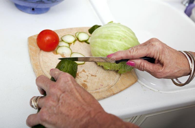 Geerntetes Bild der älteren Frau Gemüse auf Schneidebrett in der Küche hackend stockfoto