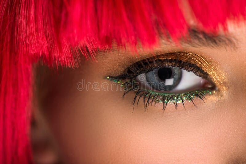 geerntetes Bild der attraktiven Frau mit dem roten Haar und des Makes-up, das Kamera betrachtet stockfoto