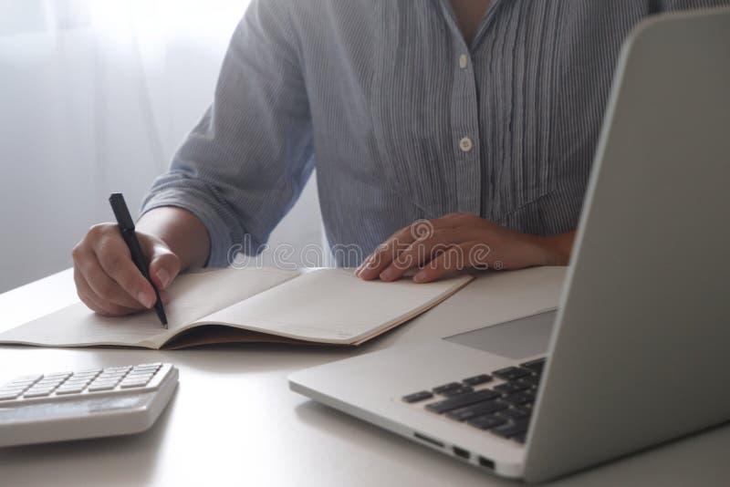 Geerntetes Bild der Berufsgeschäftsfrau arbeitend in ihrem Büro über den jungen weiblichen Manager des Laptops, der Gerät des tra stockbild