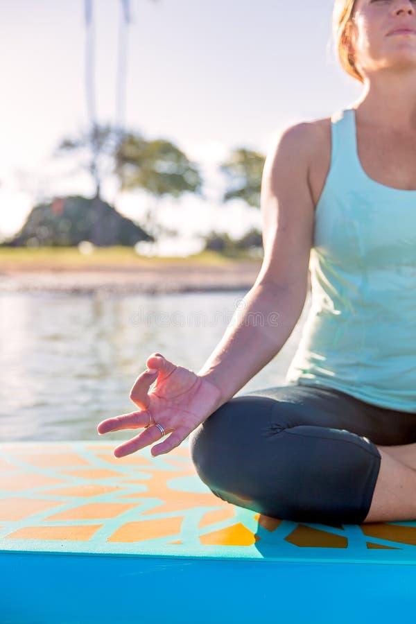 Geerntetes Bild der Frau auf dem Wasser in der Yogameditation stockbilder