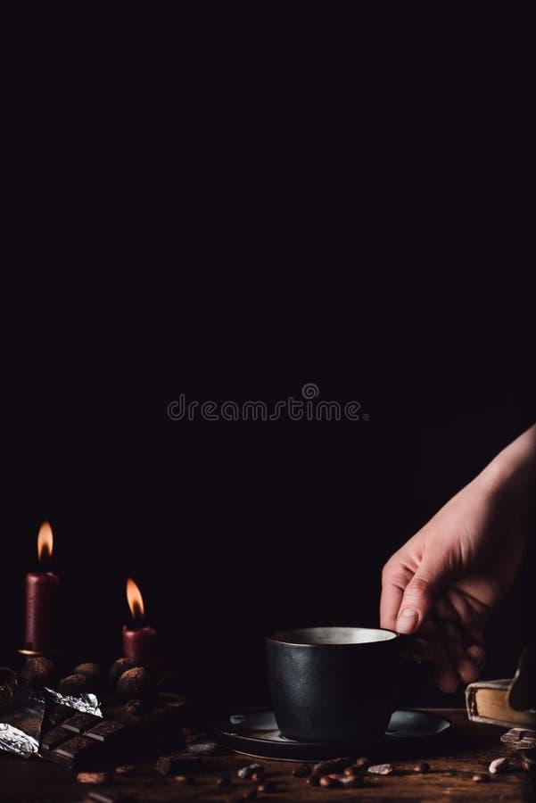 geerntetes Bild der Frau Tasse Kaffee am Holztisch mit Schokolade, Trüffeln, Kaffeebohnen, Kerzen und Buch halten lizenzfreie stockbilder