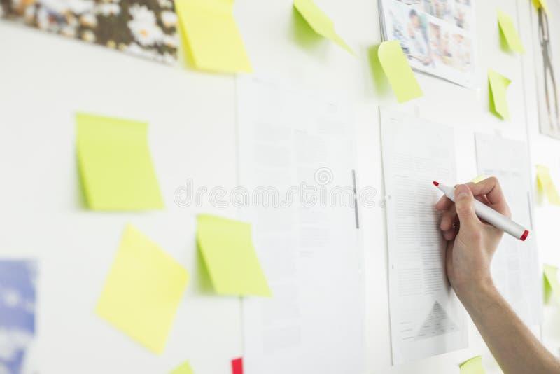 Geerntetes Bild der Handschrift des Geschäftsmannes auf Papier im Büro stockbilder