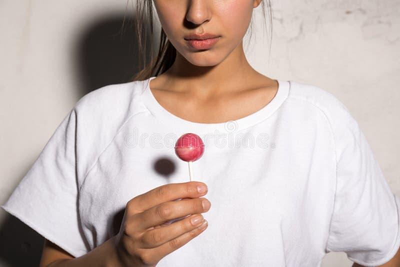 Geerntetes Bild der jungen Hippie-Frau, die Süßigkeit hält lizenzfreie stockfotos