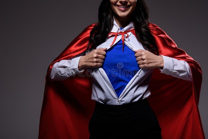 geerntetes Bild der Supergeschäftsfrau im roten Kap, das blaues Hemd zeigt stockbilder