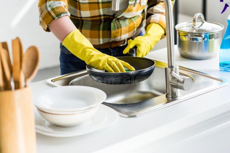 geerntetes Bild der waschenden Bratpfanne der Frau stockbilder