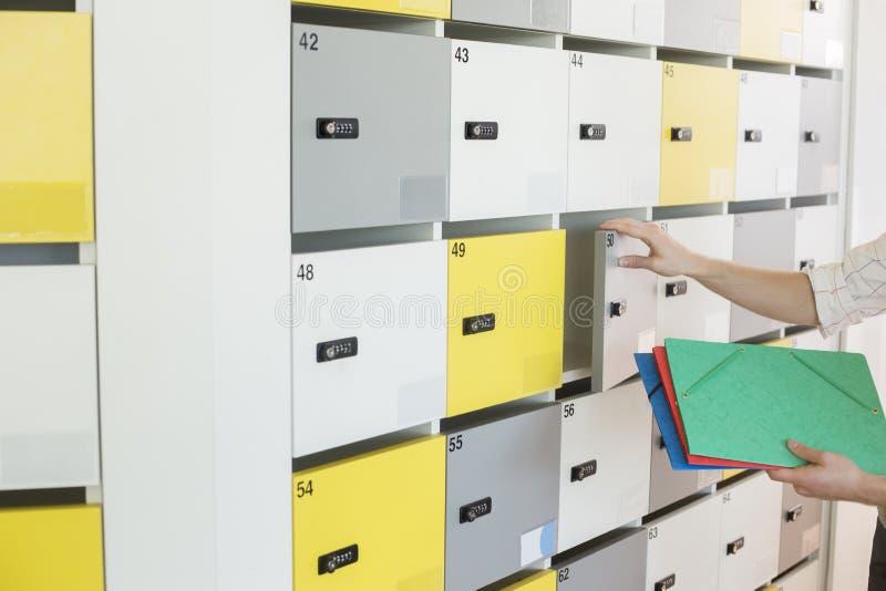 Geerntetes Bild des Geschäftsmannes Dateien in Schließfach im kreativen Büro einsetzend stockfotos