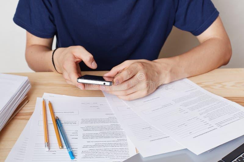 Geerntetes Bild des intelligenten Telefons in Mann ` s Händen Beschäftigtes männliches enterpreneur sitzt am Arbeitsplatz, benutz stockbilder