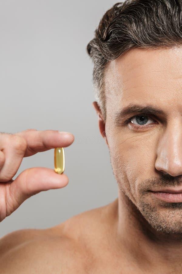Geerntetes Bild des reifen Mannes, der Pille hält Schauen der Kamera stockfotografie