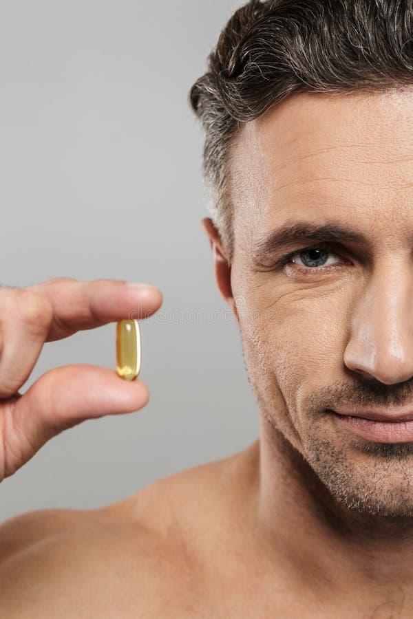 Geerntetes Bild des reifen Mannes, der Pille hält Schauen der Kamera lizenzfreie stockfotos