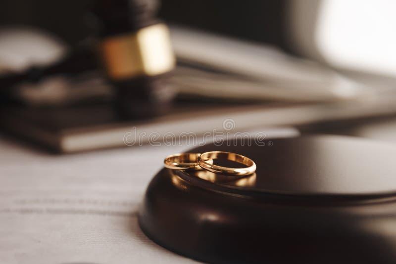 Geerntetes Bild des Scheidungsrichters Hammer auf goldenen Ringen am Schreibtisch im Gerichtssaal schlagend stockbilder