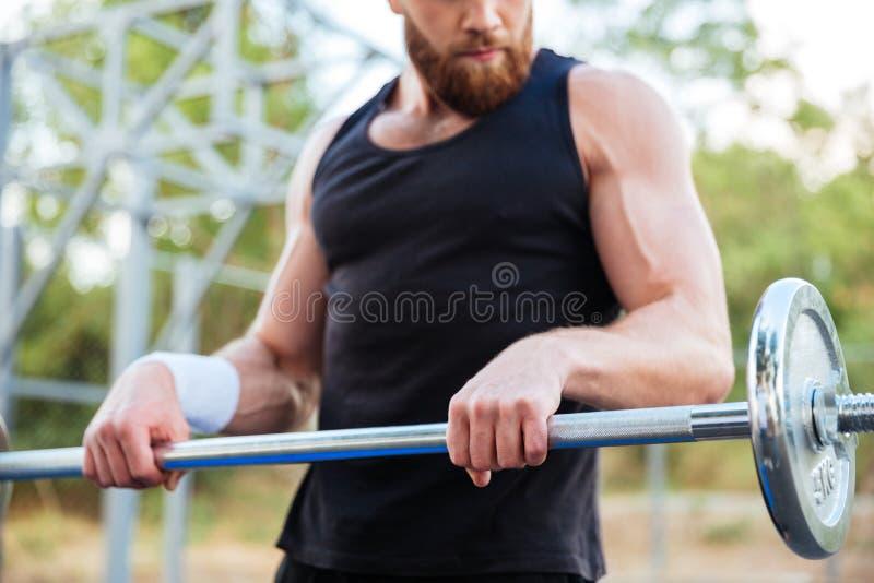 Geerntetes Bild eines ernsten jungen bärtigen Mannathletentrainierens lizenzfreies stockfoto