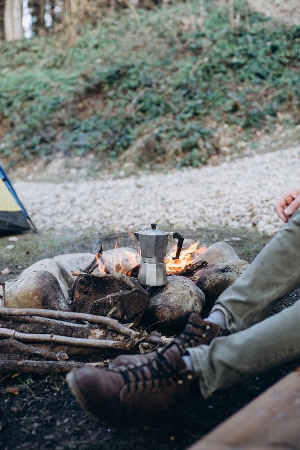 Geerntetes Bild im Freien des Forschers des jungen Mannes, der nahe zum Feuer zubereitet Hei?getr?nk in den Bergen sitzt Konzepta lizenzfreie stockbilder