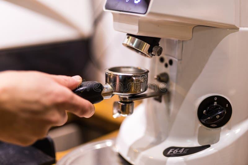Geerntetes Bild von barista frischen Kaffee in Bajonett in der Kaffeestube reibend stockfotos