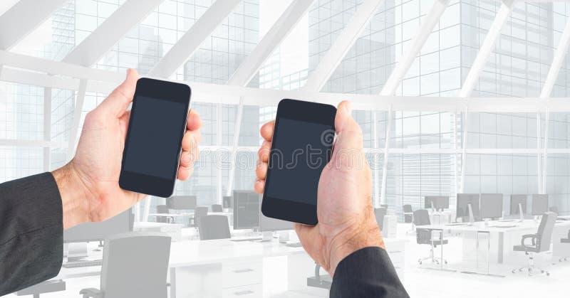Geerntetes Bild von den Händen, die intelligente Telefone im Büro halten stockbilder