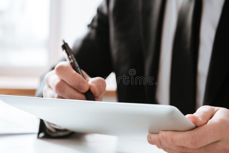 Geerntetes Bild von Geschäftsmannschreibensanmerkungen lizenzfreies stockbild