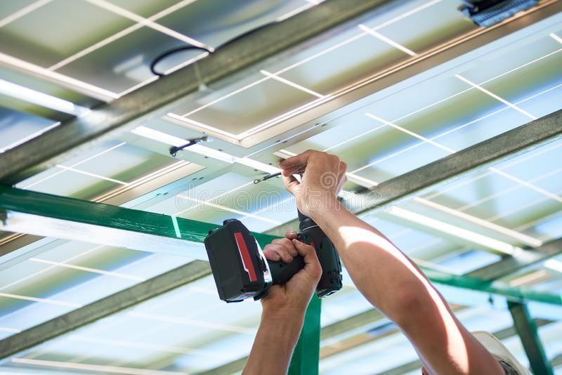 Geerntetes Foto der H?nde der Arbeitskraft unter Verwendung des Bohrger?ts durch die Sonnenkollektorinstallierung lizenzfreie stockbilder
